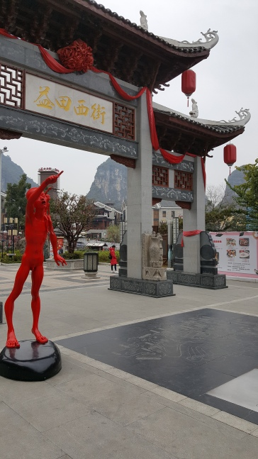 A red sculpture of a naked boy pointing at the sky stands in front of a Chinese gate that leads to a bridge in Yangshuo, China.