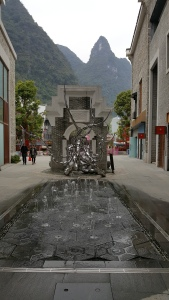 Image of an art piece in downtown Yangshuo, China. It is a chrome sculpture in front of a Chinese style wall. The sculpture has tentacles that reach out over a fountain.