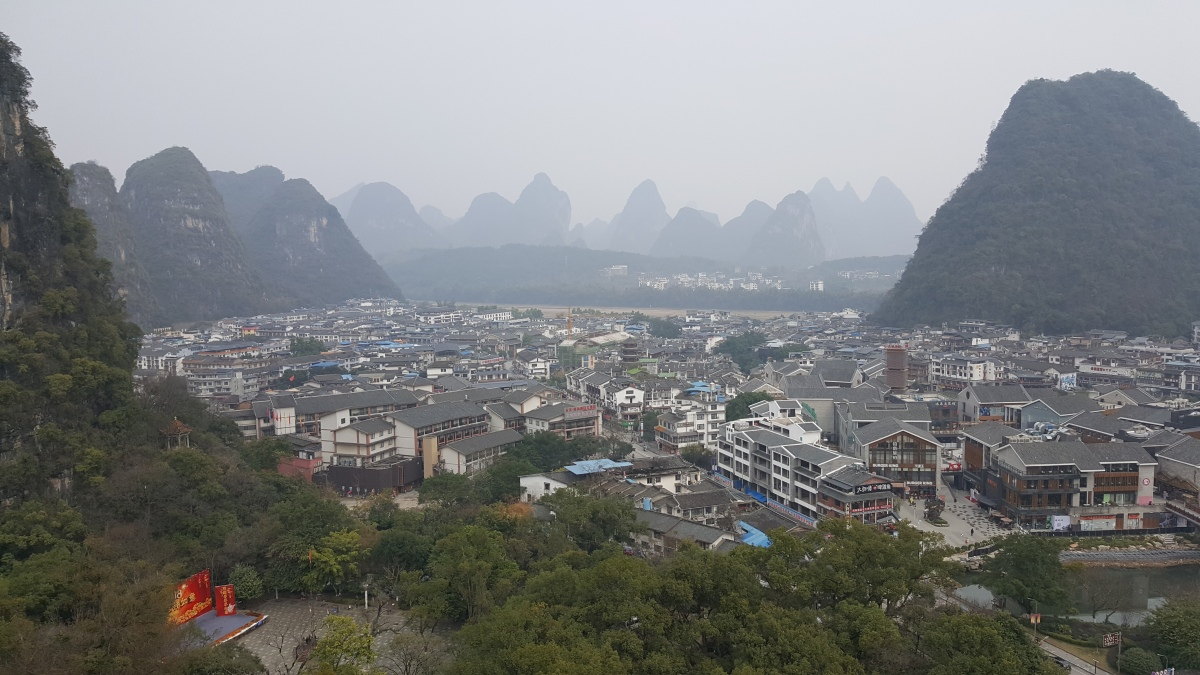 Picture from the top of Xi Lang Mountain. It shows a birds-eye view of the town in Yangshuo, China. The Li River and many karst mountains can be seen surrounding the city.