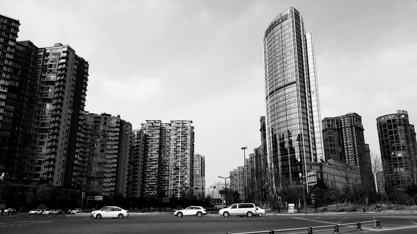black and white photo of sky scrapers in Chengdu, China. there are only a few cars and no people