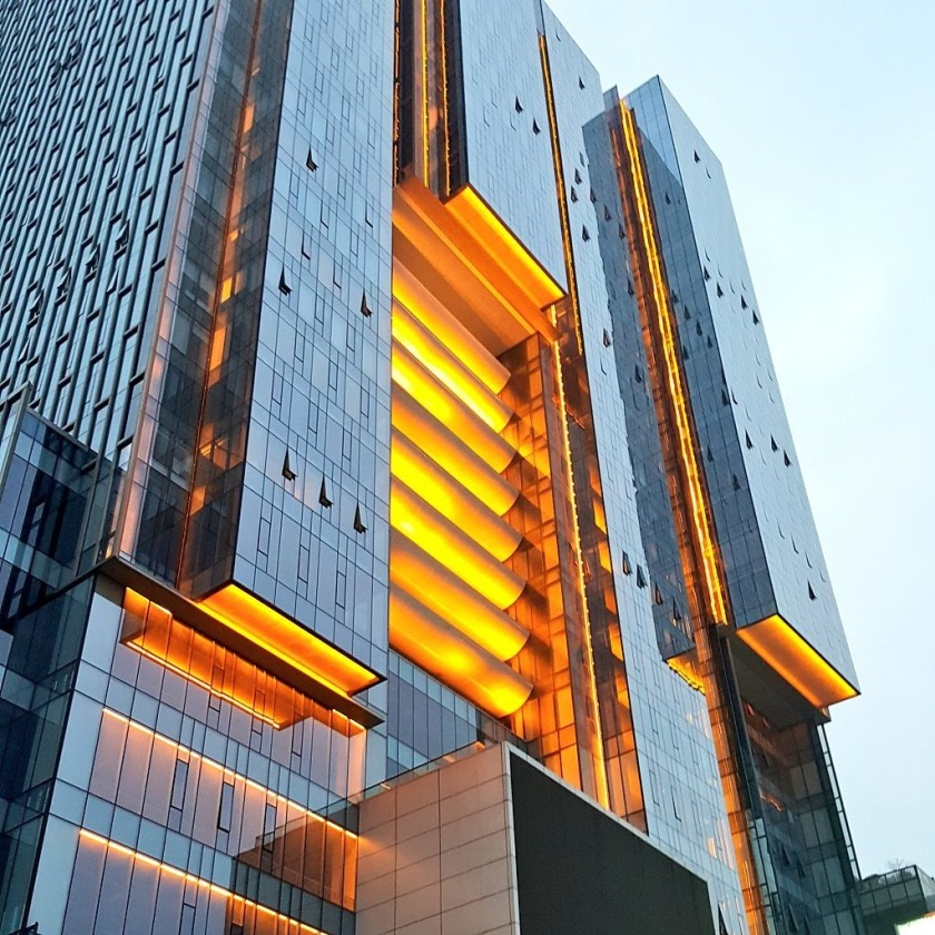partial image of the side of a building in Chengdu, China. it is blue and orange with a light blue sky in the background