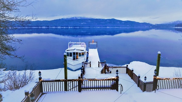 A deck covered in snow overlooking a blue lake. The deck is connected to a dock that juts into the lake. Attached to the dock is white boat. Mountains can be seen in the background.