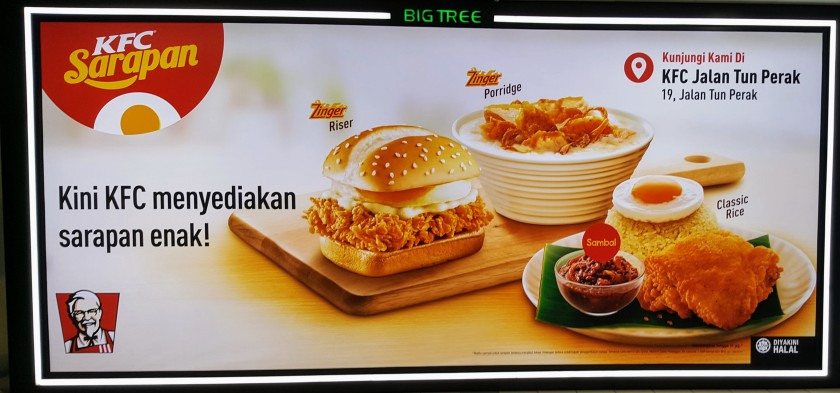 Photo of a KFC advertisement with Malaysian writing. The images show an egg and fried chicken sandwich, a bowl of porridge, and a plate titled Classic Rice which features a banana leaf topped with a pile or rice with a poached egg on top, large piece of fried chicken, and a bowl of Sambal.
