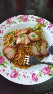 A dish with a rim of painted, pink flowers filled with Cantonese duck noodles: slices of red duck on top of dark noodles