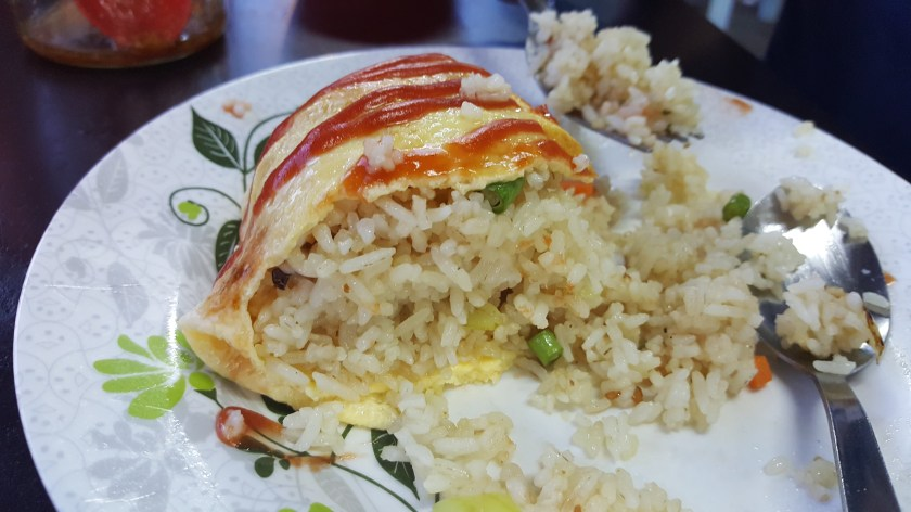 A plate with an omelet cut in half. Inside of the omelet is Chinese fried rice. On top of the omelet are decorative lines of katchup
