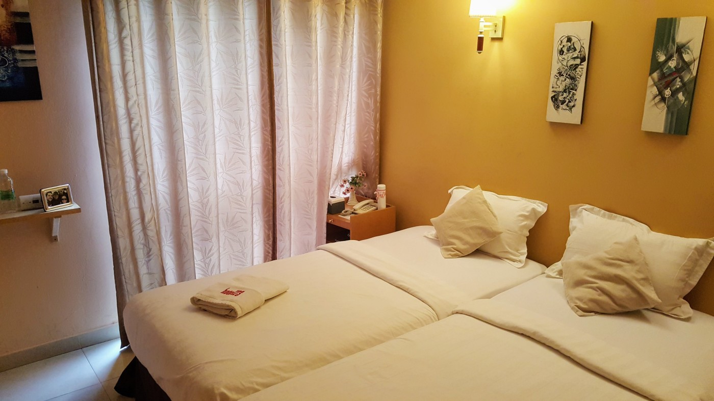Hotel room with yellow wall and some art, two twin beds pushed together with white sheets, a bedside table with fake flowers and a phone on it, a shelf on the wall with a framed photo and Carbon Monoxide Detector.