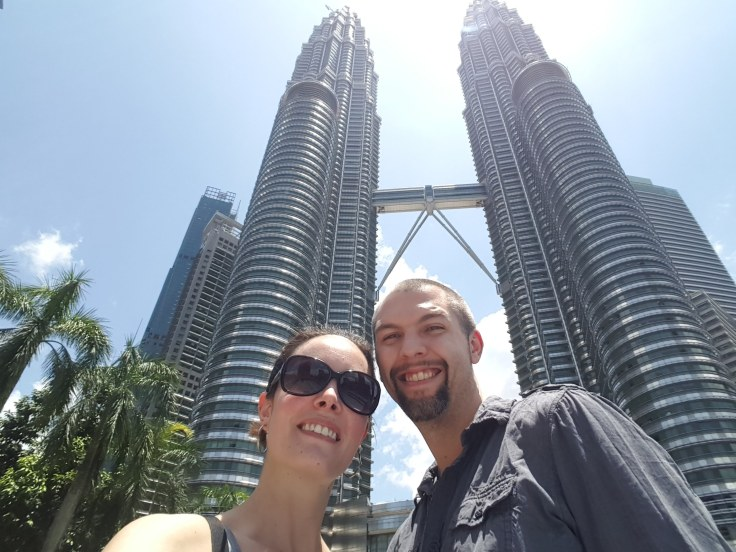 Man and woman standing outside of the Petronas Twin Towers in Kuala Lumpur's city center.