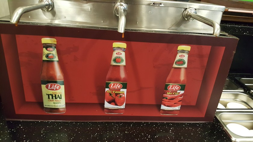 Condiment dispenser at KFC. There are three nozzles with a picture of a bottle underneath each one. One bottle is labeled Thai chili, another Tomato Sauce, and the other Chili Sauce.