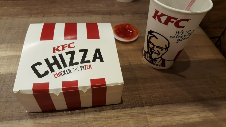 "A white box with red stripes, labeled ""KFC Chizza Chicken x pizza"" sits unopened on a table. Next to it is a small ramekin filled with a red sauce and a white cup with a picture of the KFC Colonel and labeled ""KFC. It's so refreshingly good"""