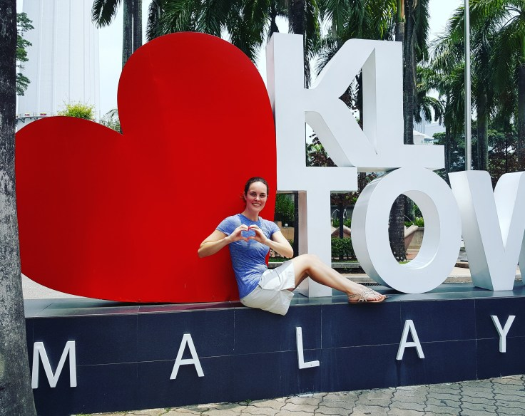 "Woman sitting in front of ""I Heart KL Tower, Malaysia"" sign"